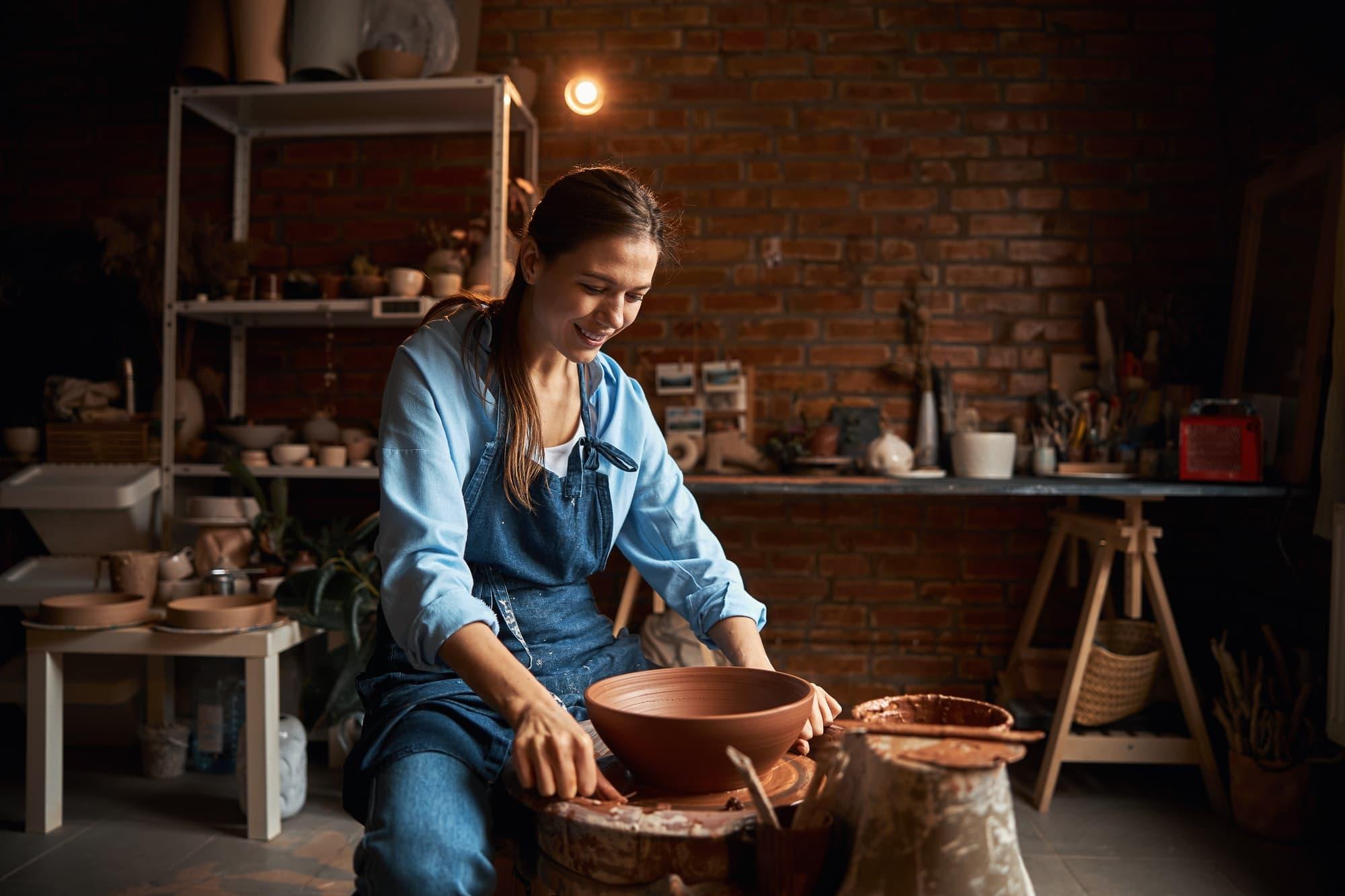 Beautiful Caucasian craft woman modeling ceramic bowl in modern pottery workshop
